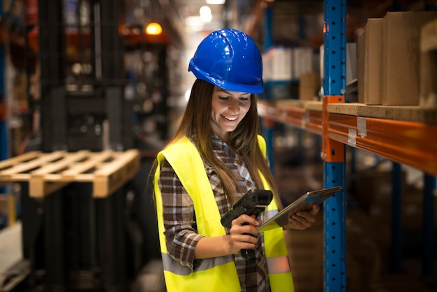 Smiling female worker holding tablet and bar code scanner checking inventory in distribution warehouse
