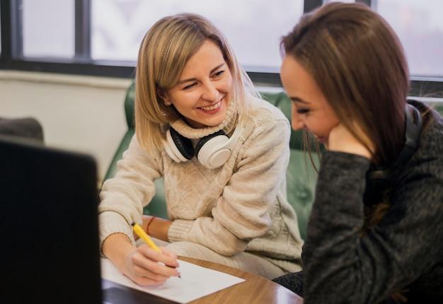 Улыбающиеся женщины в наушниках на шее смотрят на ноутбук