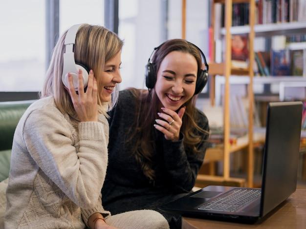 Улыбающиеся женщины в наушниках смотрят на ноутбук