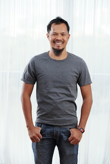 Smiling filipino man standing with thumbs in pockets in front of brightly lit window