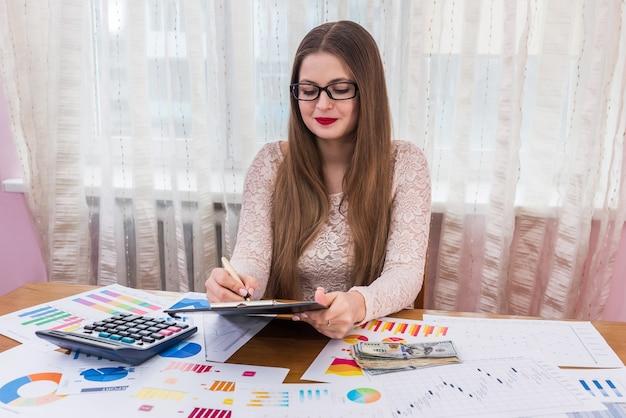 Улыбающийся финансовый аналитик делает заметки на планшете