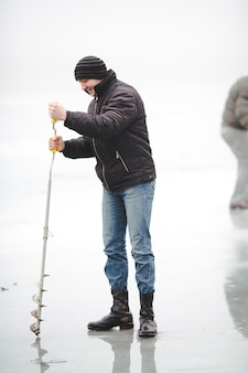Smiling fisher drills a hole in the ice