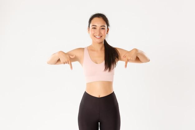 적합 하 고 슬림 한 여성 피트 니스 강사, 체육관에서 아시아 여자 운동 웃 고 뭔가 보여주는, 아래로 손가락을 가리키는, 흰색 배경에 서.