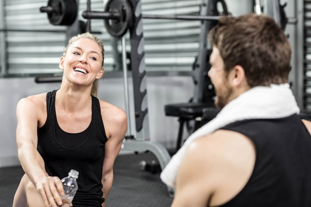 Smiling fit couple sitting at crossfit gym