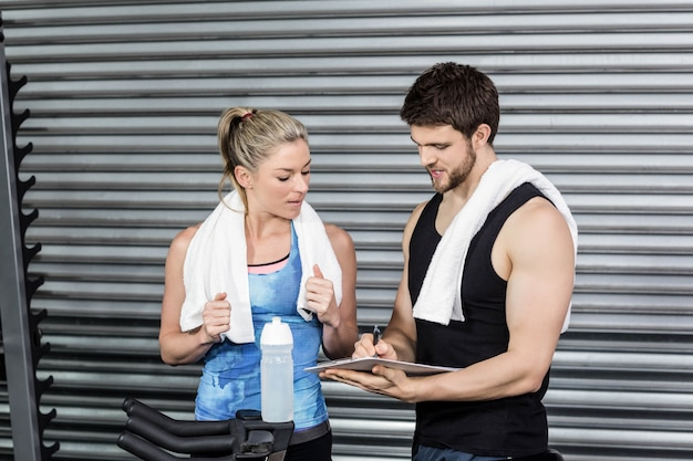 Smiling fit couple taking notes at gym