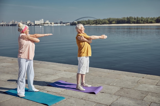 Smiling fit elderly lady and her spouse doing a cross-body shoulder stretch