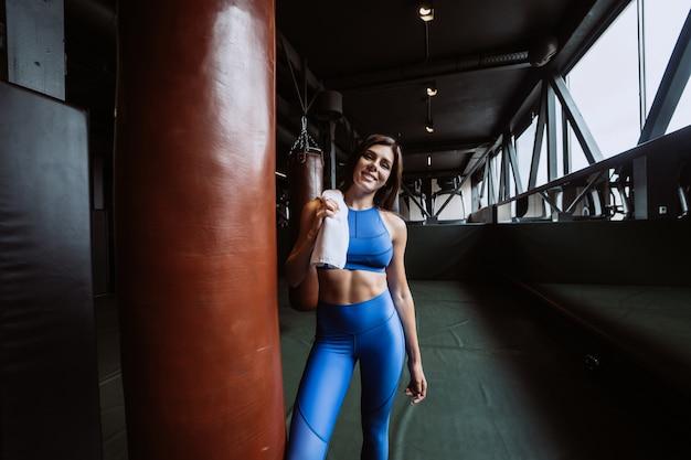 Усмехаясь подходящая девушка держа полотенце и отдыхая в спортзале около груши