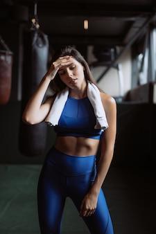 Усмехаясь подходящая девушка держа полотенце и принимая остатки в спортзале.