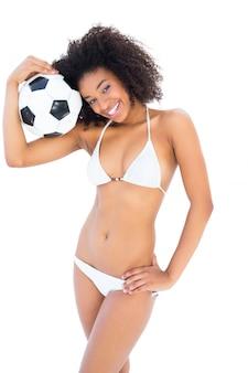 축구를 들고 흰색 비키니에 맞는 여자를 웃 고