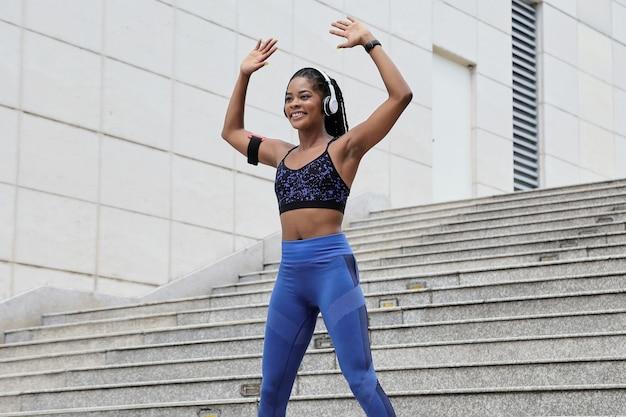 훈련 전에 워밍업을 위해 점프 잭 운동을 하 고 맞는 꽤 젊은 흑인 여성 미소