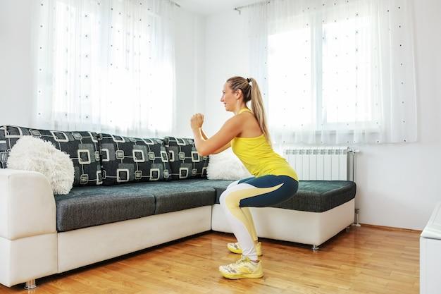 Улыбаясь подходит спортсменка, делая приседания дома.
