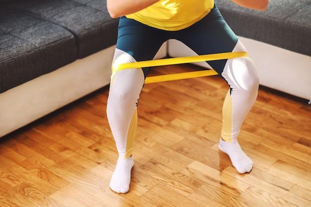 腰に手を当てて家に立って、脚でパワーラバーを伸ばしている笑顔のフィットスポーツウーマン。彼女はフィットネスエクササイズをしています。