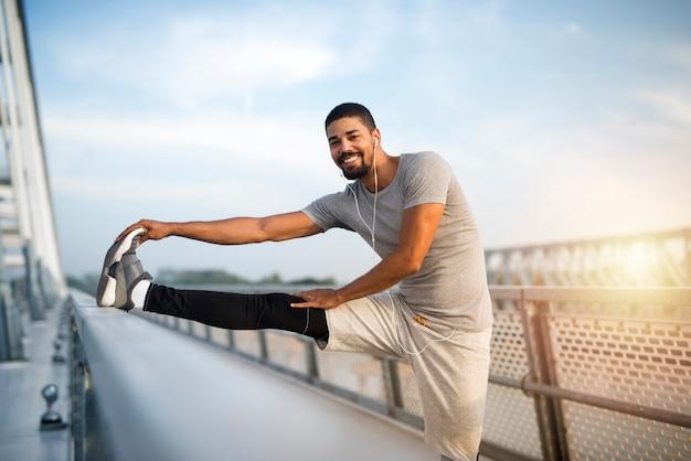 실행하기 전에 그의 다리를 스트레칭 훈련 아프리카 미국 선수를 위해 워밍업 맞는 스포티 한 남자를 웃고.