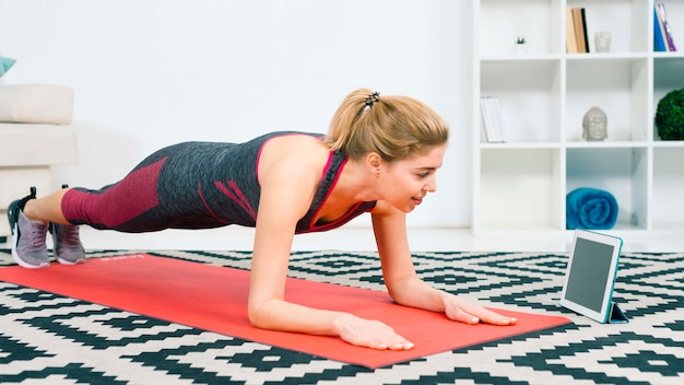 Smiling fit woman doing plank by looking at digital tablet on red mat at home in the living room