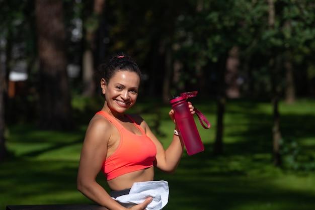 屋外でのトレーニングの後、笑顔のフィット女性の飲料水。良好な水分補給と減量の概念を維持する