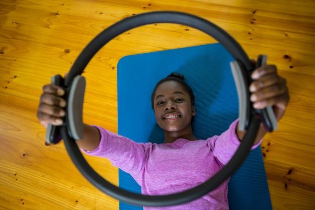 Улыбающаяся женщина, тренирующаяся с кольцом для пилатеса на коврике