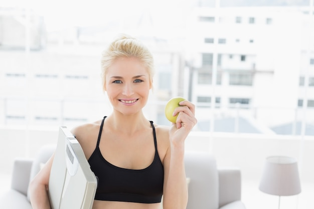 Smiling fit woman holding scale and apple in fitness studio