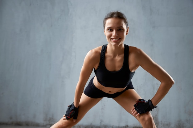 Smiling fit woman practicing legs stretching