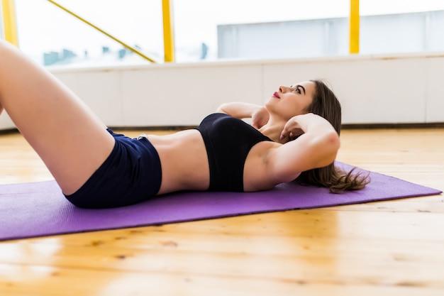 그녀의 몸과 균형 요가 연습 웃는 여자는 바닥에서 제기
