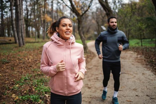 彼女の友人の前で速く走っている笑顔のフィット女性。彼らはマラソンのために運動しています。