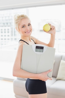 Smiling fit woman in sportswear holding scale and apple