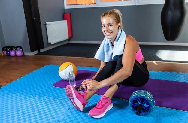 フィットネスクラスのスニーカーに靴紐を結ぶ笑顔のフィット女性。健康的なライフスタイルフィットネスの概念