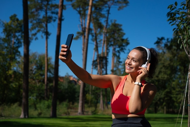 Smiling fit woman with headphones makes selfie while having reat in the beautiful park. relaxation outdoor.