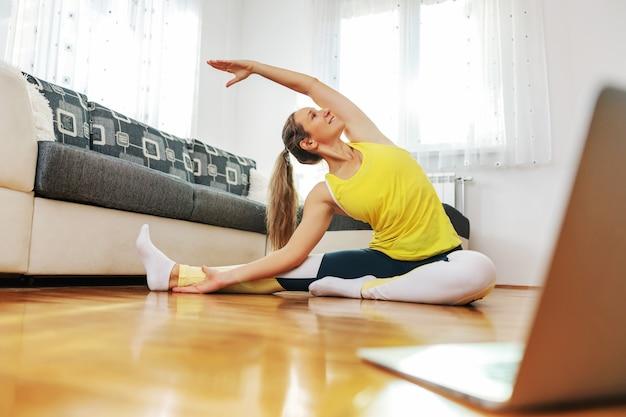 自宅の床に座って頭から膝までのヨガのポーズをとり、オンラインクラスをフォローしている笑顔のフィットヨギ女性。