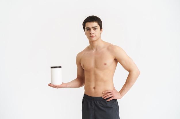 Улыбающийся молодой спортсмен без рубашки показывает банку с протеином для фитнеса над белой