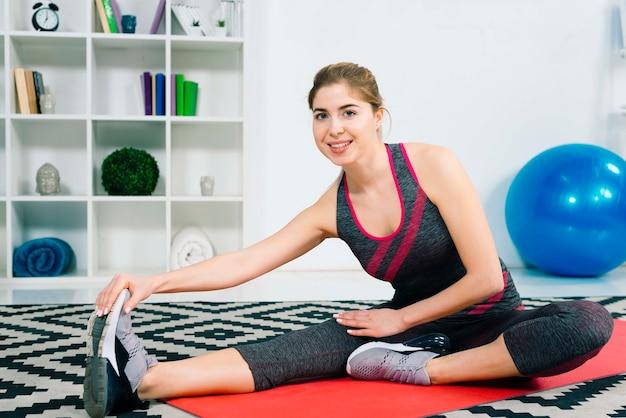 Улыбаясь подходит молодая женщина делает тренировки в гостиной