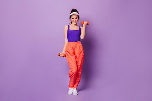 Sorridente istruttore di fitness dimostra esercizi bicipiti con manubri