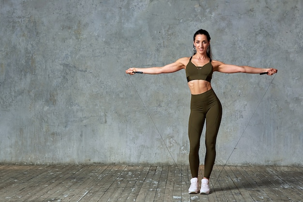 Smiling fitness model posing in full-length gymnasium against a gray wall with jumpers in her hands,fitness concept