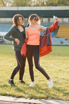 Smiling fitness mother and teen daughter together posing at stadium