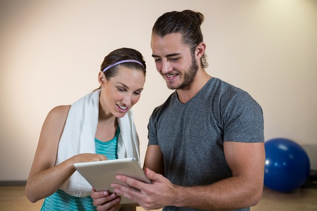 Smiling fitness trainer and woman using digital tablet