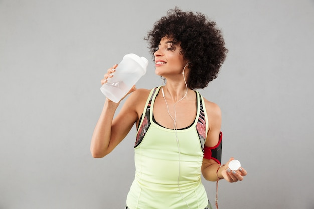 Smiling fitness woman drinking water with closed eyes