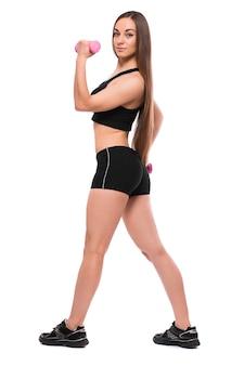 Улыбающаяся женщина фитнеса, тренирующаяся с гантелями, изолированными на белом фоне