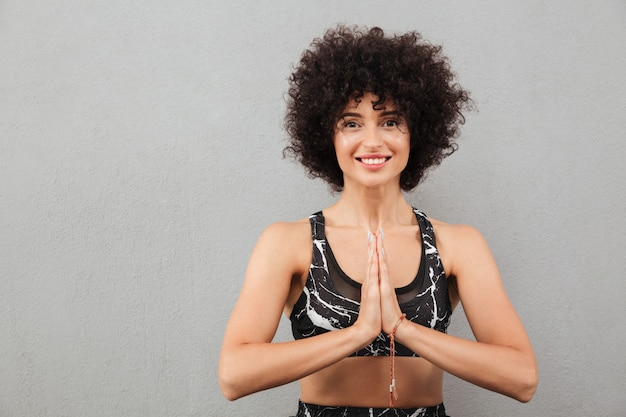 Smiling fitness woman holding hands in pray gesture