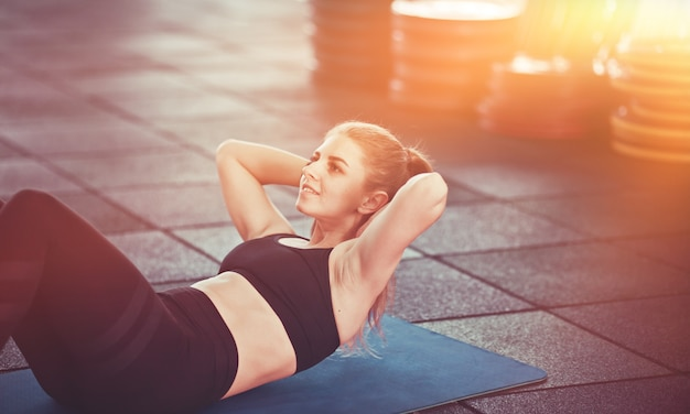 ジムのマットの上に横たわっている腹筋のためにねじれをしているスポーツウェアの笑顔のフィットネス女性