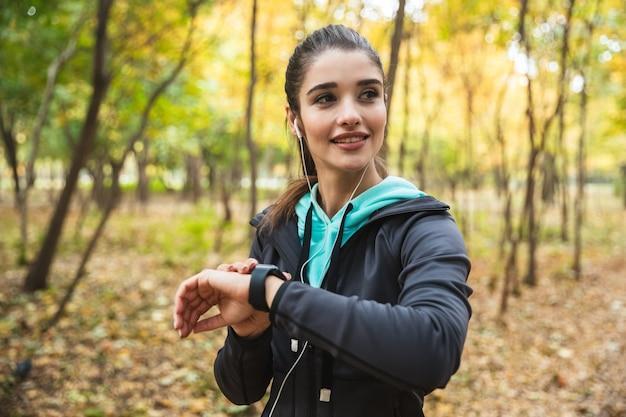 Улыбающаяся женщина фитнеса слушает музыку в наушниках, проверяет умные часы, стоя в парке