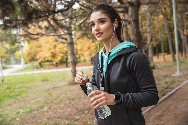 公園に立っている間、イヤホンで音楽を聴き、水のボトルを保持しているフィットネス女性の笑顔