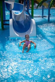A smiling fiveyearold girl in a pink swimsuit floating on an inflatable circle from a water slide in...