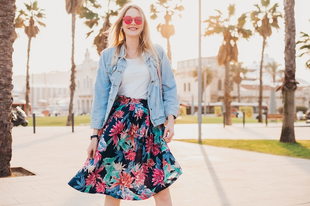 Smiling flirting woman walking in city street in stylish printed skirt and denim oversize jacket wearing pink sunglasses