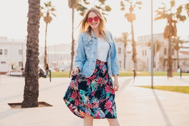 Smiling flirting woman walking in city street in stylish printed skirt and denim oversize jacket wearing pink sunglasses