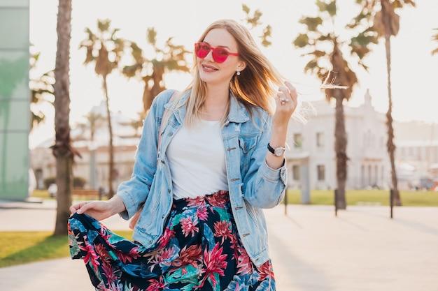 세련된 프린트 스커트와 핑크색 선글라스를 착용 한 데님 특대 재킷으로 도시 거리에서 걷는 웃는 유혹 여자