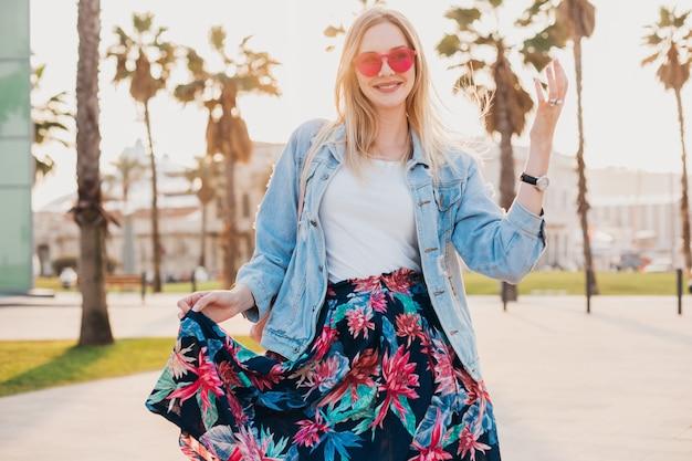 Улыбающаяся флиртующая женщина гуляет по городской улице в стильной юбке с принтом и джинсовой куртке oversize в розовых солнцезащитных очках