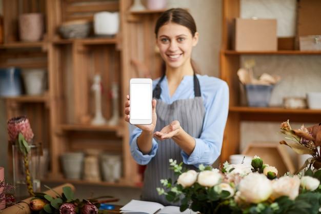 Smiling florist presenting mobile app