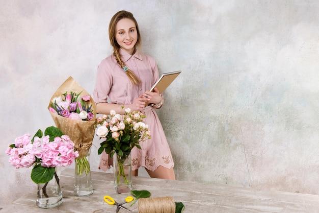 花屋のチェックリストと笑顔の花屋。フラワーショップでノートを持つビジネスウーマン。中小企業経営、女性マネージャー、時間管理、花の販売コンセプト