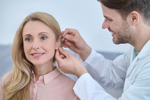 집중적으로 수염을 기른 검은 머리 남성 청력학자가 여성 환자의 귓바퀴에 보청기를 끼고 웃고 있습니다.