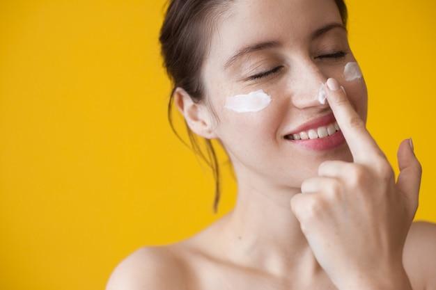 Улыбающаяся веснушчатая женщина надевает антивозрастной крем для лица
