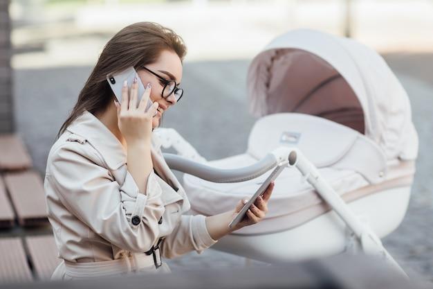 公園のベビーカーの近くのベンチで電話で作業している笑顔のフリーランサーのお母さん。